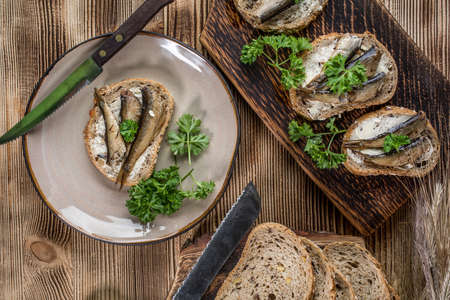 Sandwich with sprats on wooden table. Archivio Fotografico