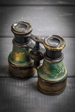 Old binoculars covered with patina on a gray woodenbackground.
