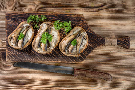 Sandwich with sprats on wooden table. Top view. Stock fotó