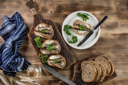 Sandwich with sprats on wooden table. Top view. Archivio Fotografico