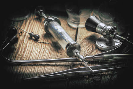 Retro syringe, stethoscope and medical cupping glass on a wooden table. Shallow depth of field. Vintage style.