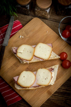 Sandwich with ham and smoked cheese on cutting board.