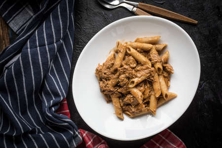 Penne pasta with pork sauce on a black background.