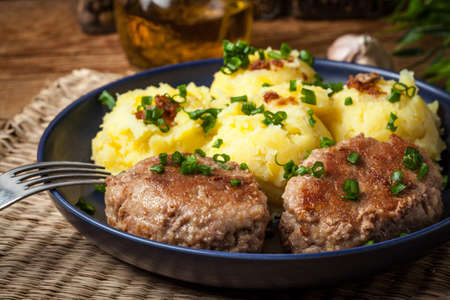 Meatballs served with boiled potatoes on a plate. Stock Photo