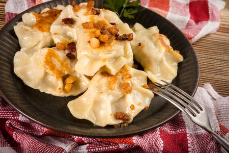 Fried dumplings (pierogi) with meat filling sprinkled with greaves.