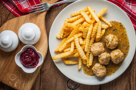 Meatballs with french fries in dill sauce and cranberry jam. Selective focus. Top view.