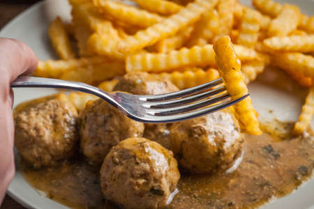 Meatballs with french fries in dill sauce and cranberry jam. Selective focus. Imagens