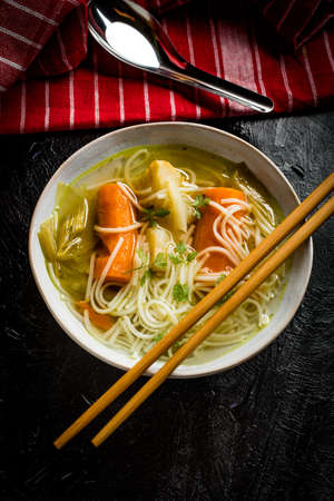 Tasty home broth with vegetables and noodles.