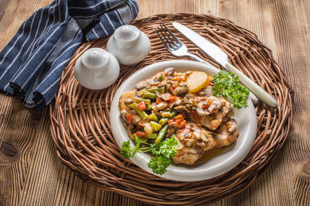 Chicken fillet with stewed vegetables on a white plate. Imagens