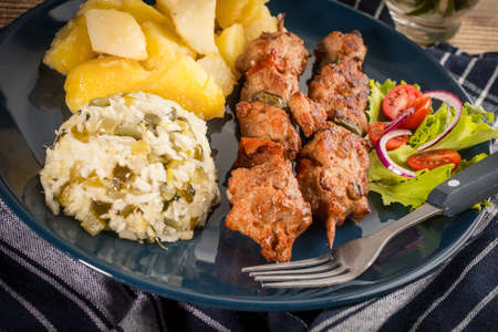 Shish kebabs - grilled meat, fried potatoes and vegetables.