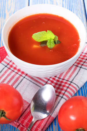 Tomato soup on wooden table. Selective focus.