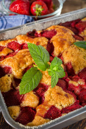 Yeast cake with strawberry in a mold. Small depth of field.
