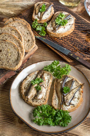 Sandwich with sprats on wooden table. Stock fotó