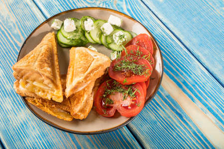 Sandwiches with cheese, tomatoes and cucumber on a plate. Stock fotó