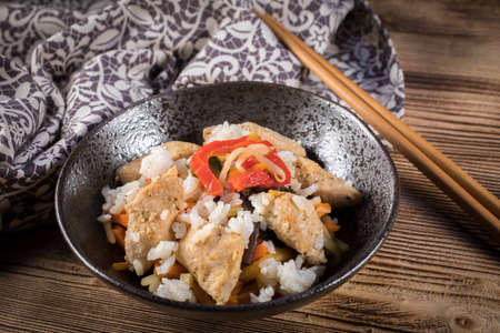 Fried chicken with rice and vegetables in bowl.