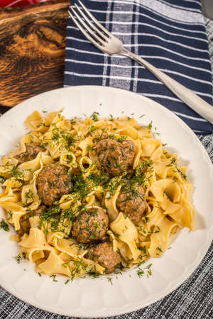 Tagliatelle pasta with pork meatballs and dill sauce. Selective focus.
