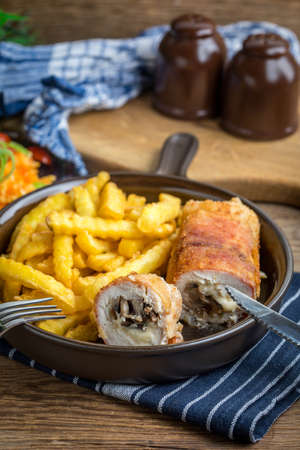 Fried chicken breast stuffed with mushrooms and cheese wrapped in ham served with fries and salad.  Small depth of field. Stockfoto