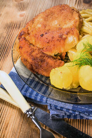Breaded chicken with potatoes and yellow beans.