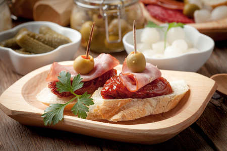 Spanish cuisine. Tapas with sliced sausage, salami, olives and parsley on a wooden table.