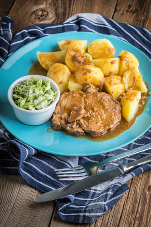 Braised meat in sauce served with boiled potatoes. Selective focus. Stock Photo