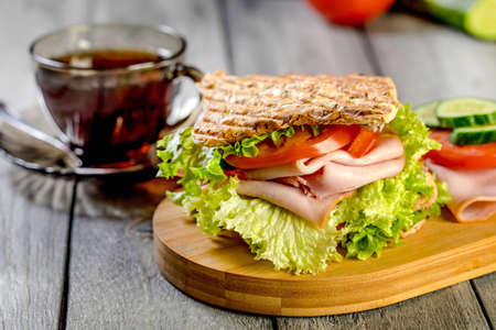 Sandwich with ham, cucumber, tomato and lettuce, with two layers of filling between three slices of toast. Reklamní fotografie - 133484172