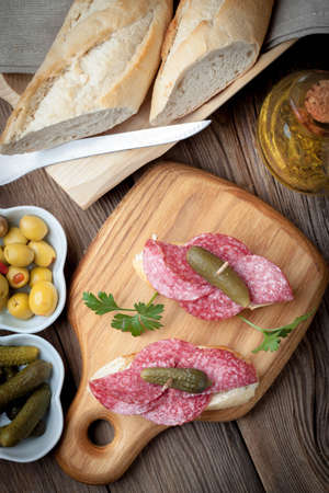 Spanish cuisine. Tapas with sliced sausage, salami, olives and parsley on a wooden table. Top view. Stockfoto