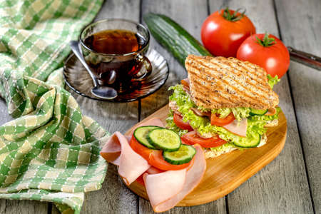 Sandwich with ham, cucumber, tomato and lettuce, with two layers of filling between three slices of toast.