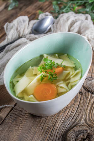 Broth - chicken soup with noodles in a bowl.