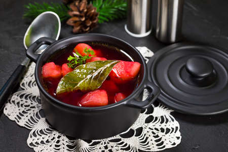 Red borscht soup in bowl on black background.