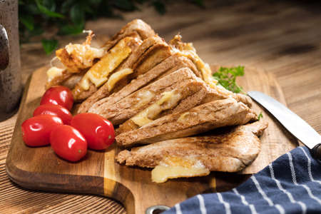 Grilled cheese sandwich on a chopping board. Shallow depth of field. Reklamní fotografie - 133484311