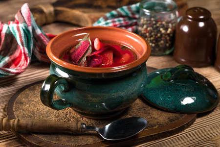 Barszcz czerwony zupa w misce na drewnianym tle.