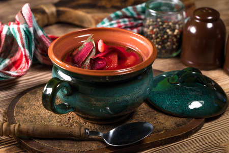 Red borscht soup in bowl on wooden background.