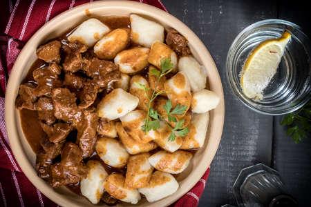 Chunky beef stew with savory sauce beside potato dumplings. Top view. Zdjęcie Seryjne