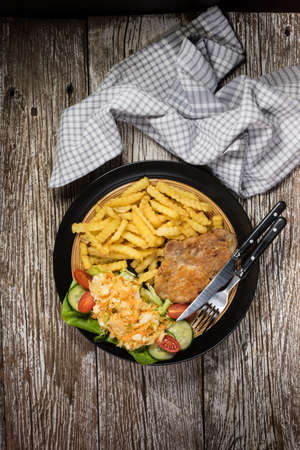 Traditional Polish dish: fried pork chop in breadcrumbs, served with fries and salad.