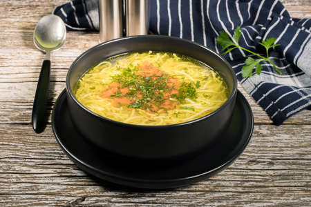 Broth - chicken soup with noodles in a dark bowl.