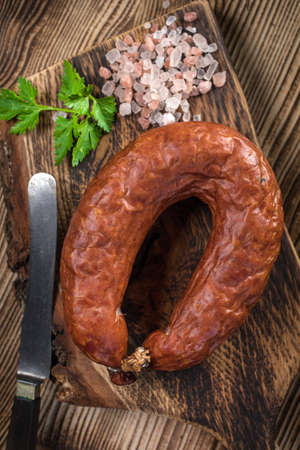 Rings of traditional, country, homemade, pork smoked sausage on a wooden cutting board.