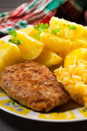 Minced pork cutlet served with potatoes and sauerkraut salad.