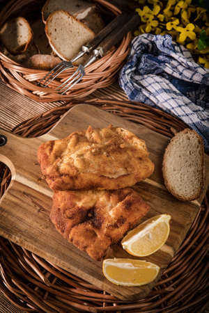 Cod fillet fried in breadcrumbs on a chopping board. 版權商用圖片