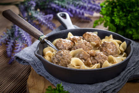 Pork meatballs with noodles in a cast iron skillet. Selective focus.