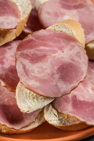 Sandwich made of wheat bread, butter and slices of dry-cured sausage. Selective focus. Archivio Fotografico