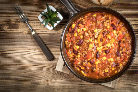 Chili con carne in a clay pan. Traditional mexican cuisine. Top view.