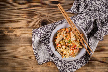 Fried chicken with rice and vegetables in bowl. Top view.