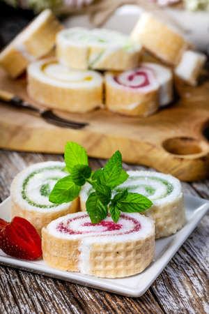Slices of homemade sweet roll with fruit jam  on wooden background.