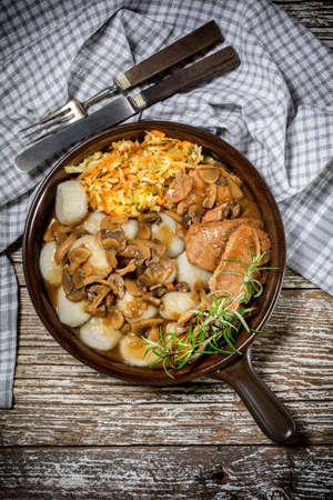 Stewed pork loin with mushrooms, served with Silesian dumplings and salad. Top view. Stock Photo