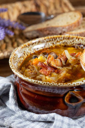 Traditional russian sour cabbage soup on wooden table. Selective focus.