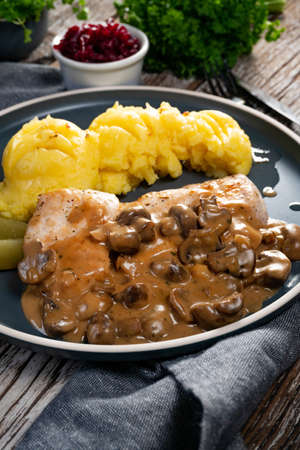 Grilled chicken breast with mushroom sauce, served with mashed potatoes and pickled cucumbers.