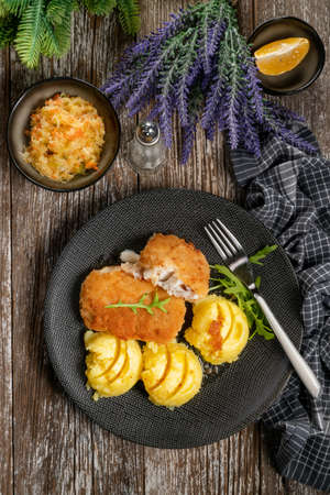 Fried cod fillet served with boiled potatoes and vegetable salad.
