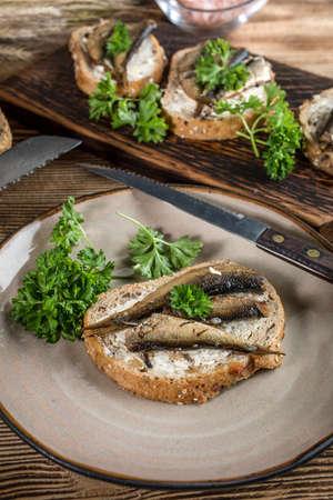 Sandwich with sprats on wooden table. Standard-Bild