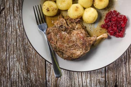Roasted duck leg with potato dumplings and cranberry. Standard-Bild