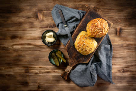 Tasty buns with cheese and sunflower seeds on wooden background.